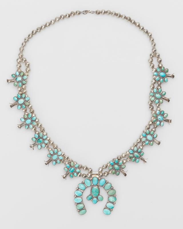 Double strand of small silver beads becomes single strand at 11 ends; 12 groups of squash blossoms overlaid with clusters of small elliptical Miami turquoises; sheet naja set with 17 Miami turquoise mounted; serrated bezels, 96 stones total in groups; silver strand ends in silver clasp. J.#395, Cat.#436.