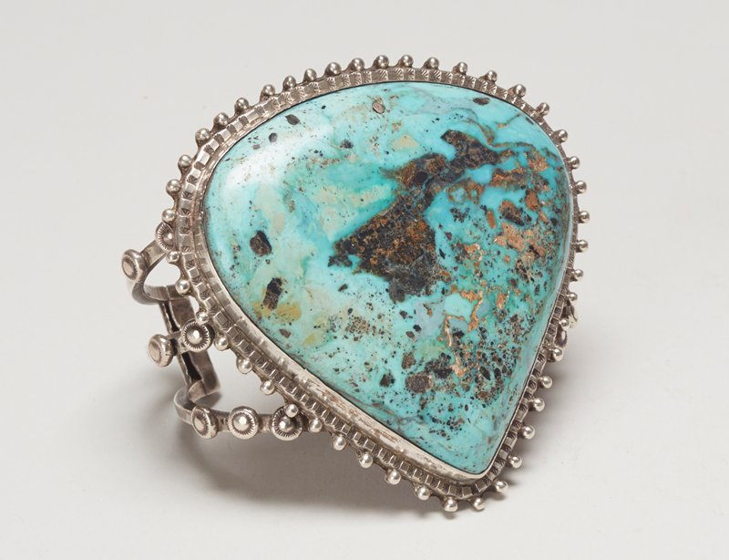 Three square wires; set with large shield-shaped turquoise; teardrop and stamped decoration.; Triple sq. wire with large shield-shaped turquoise, has hole with silver fill cat. 56,J#8