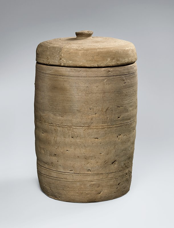 light grey ceramic vessel with incised bands running horizontally around exterior in three groups, at top, middle, and bottom; matching lid with incised bands radiating outward in two groups from central knob