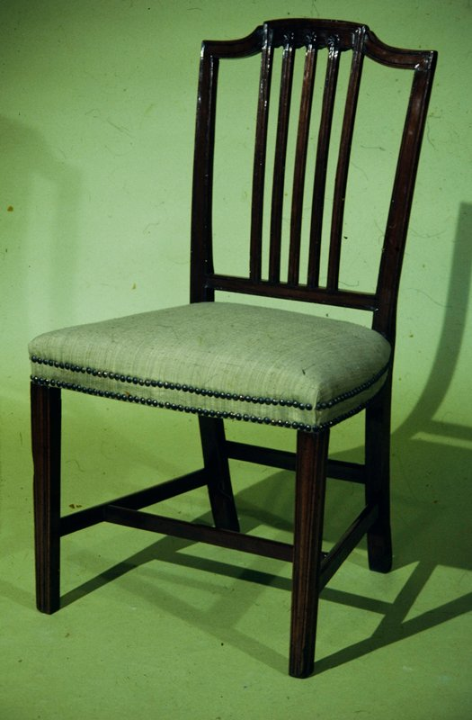 side chair, Sheraton style; open back, with five slender moulded uprights in center, the three middle ones terminating in rosettes and the outer ones joined by moulding of crest rail; moulded slightly tapering legs, braced with four stretchers; maroon colored leather seat, serpentine front, edged with double row of brass nail heads