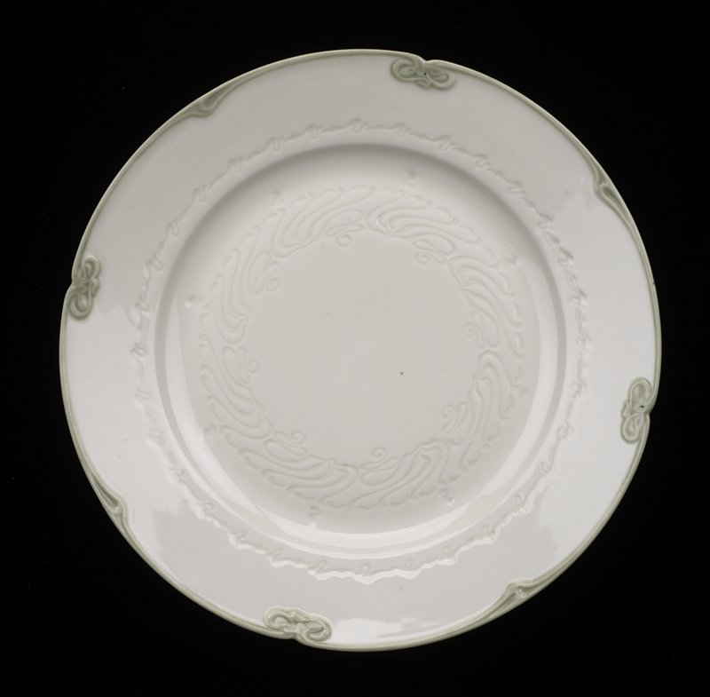 91fccad527a Cream plate with raised swirled decoration in center and edges with green  border.