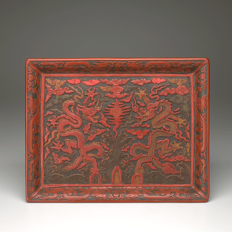 red, green and yellow carved lacquer tray with short foot and flaring edge; central design of 2 dragons flanking a flaming shou character; 6 dragons at edges with flowers on exterior