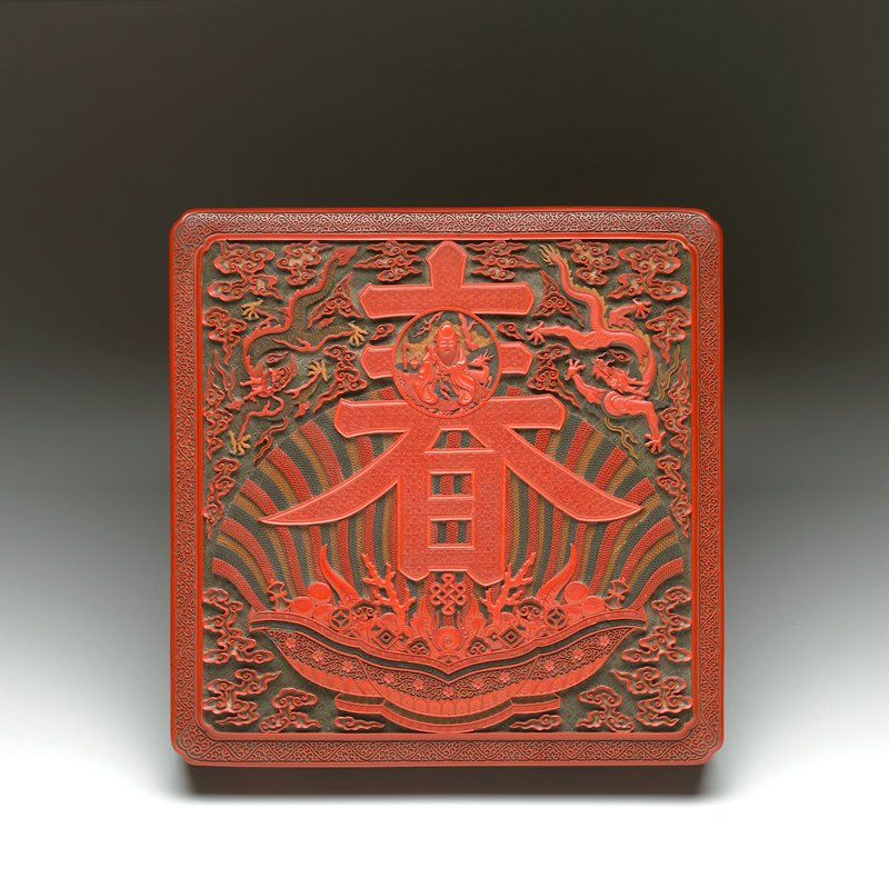 red, green, ochre and brown carved lacquer; square with indented corners; top has small medallion with Shou Lao in a large chun character, 2 dragons in clouds and radiating bowl with objects at bottom; outdoor scenes with figures on sides