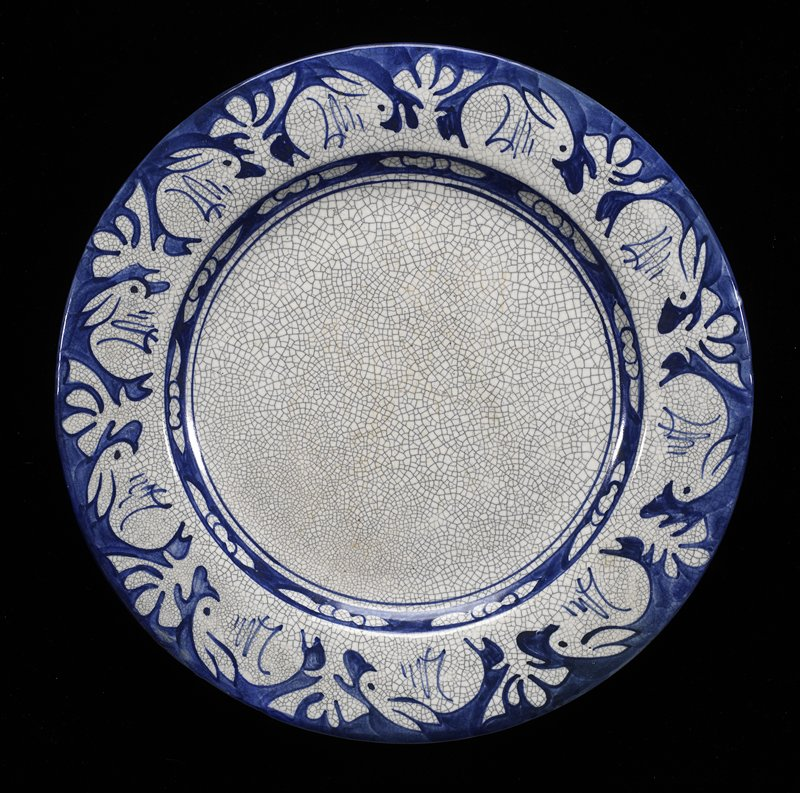 Pottery with blue painted border of alternating rabbits and plants over a white crackled glaze. Printed by Alice and Joseph Findon Smith.