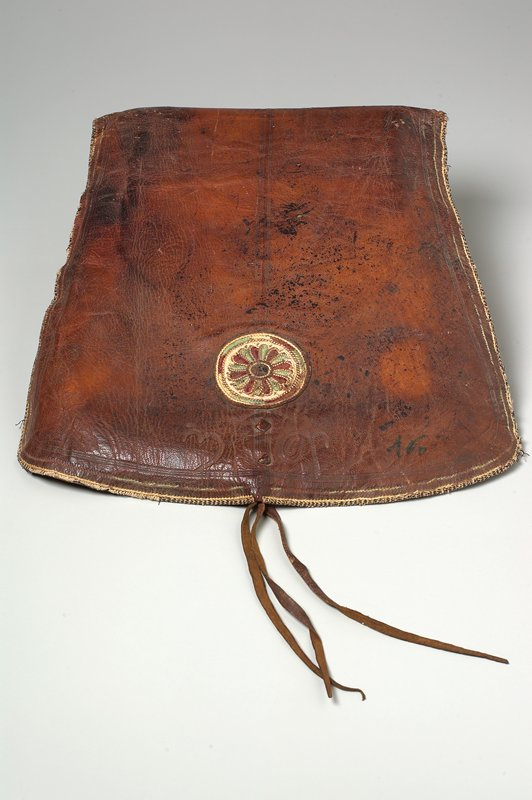 pouchlike bag with flap closure; elaborate floral medallion and organic embroidered designs on interior of flap and bag body, with one floral medallion on exterior; 2 stamped designs on front flap; 2 metal rings on strap