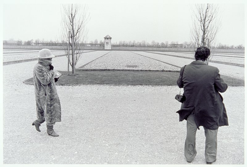 two people standing in front of long flat structure with two bare trees in background.