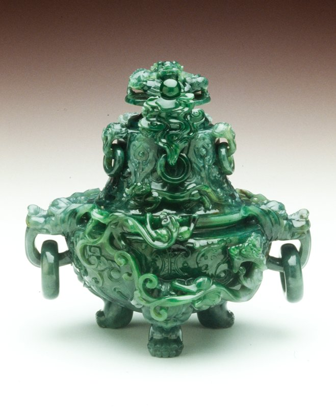 The globular body deeply carved dragon motifs in raised relief, with large animal masks and loose ring handles at the side, the high domed cover with further loose ring handles and with coiled dragon finial, the stone with very bright green patches used in the carving.