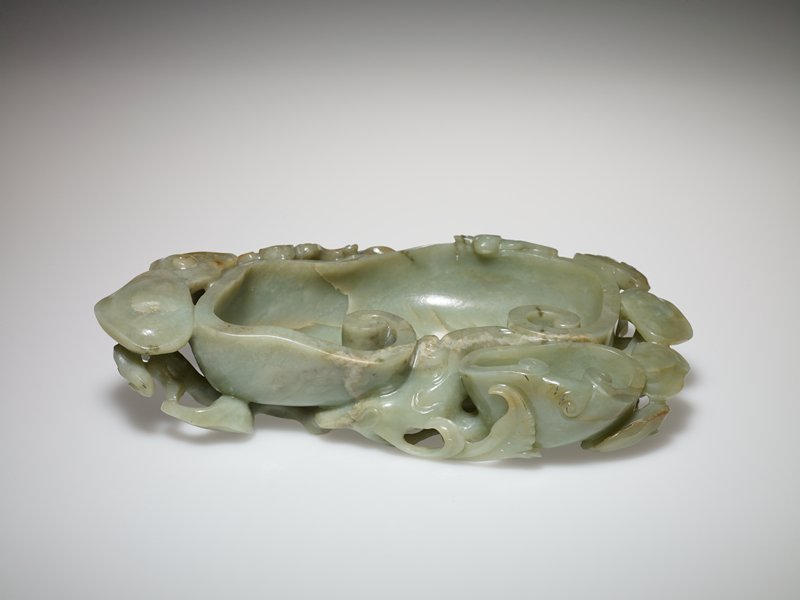 The large central shallow bowl carved in the form of a Ruyi head, with smaller bowls and fungus and bat motifs around the edge, the dull gray-green stone with cloudy russet markings. Former Classification: Jade