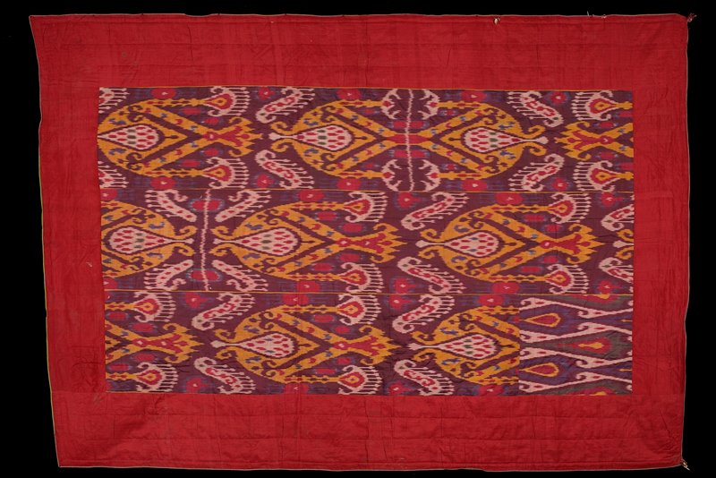ikat central panel in red, yellow, blue, purple, green; central panel surrounded by red border, edges bound with narrow strips of purple and green fabric; piece of another ikat fabric in corner