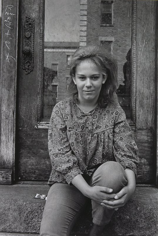 young woman in flowered blouse, seated on a step in front of a door; grafitti on door jamb to left of doorknob