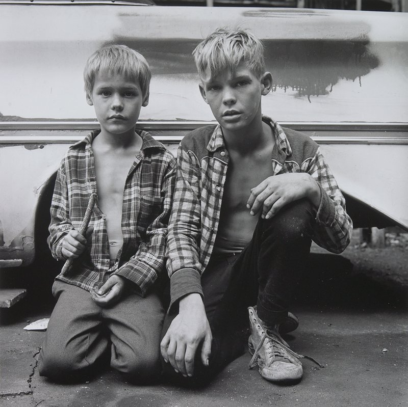 two blonde boys wearing unbuttoned plaid shirts, seated on the ground in front of a car; boy at left holds a stick