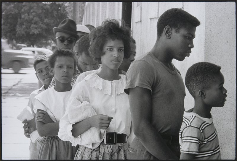 black teenagers and children standing in line; young woman with short hair wearing a white blouse at center