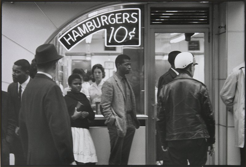 "seven figures, including one girl, standing in front of a window with a neon sign reading ""HAMBURGERS 10¢"""