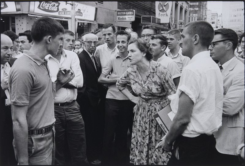 large crowd of people in a city street; woman at right in a flowered dress confronts a smoking man at left