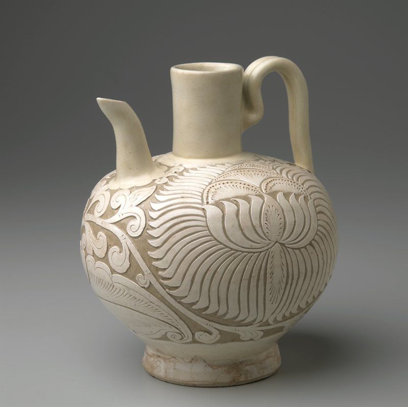 white slip-decorated ewer with low flaring foot and globular body; strap handle; curved spout; body deeply carved with scrolling vine and two large lowers; light grey clay
