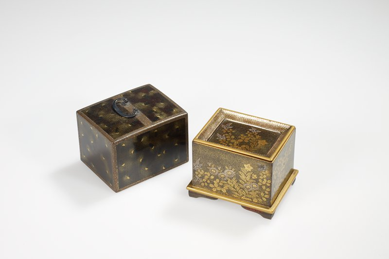 Toilet box in shape of casket, cover with metal handle, inside decorated around and on top of a fitted tray with flower sprays. Aventurine and gold. Cover mottled gold and black with crescent moons.