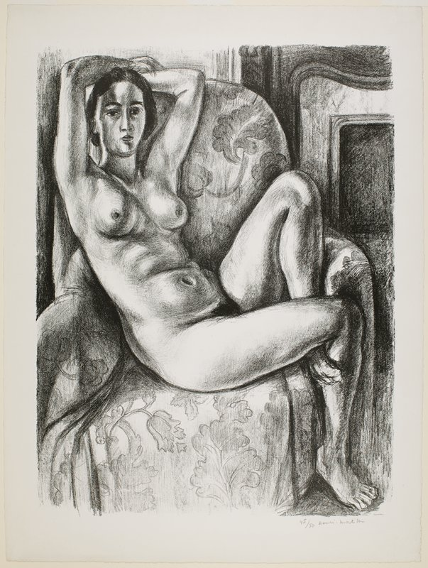 nude woman seated, with her hands on her head, in a chair covered with flowered throw; fireplace at right