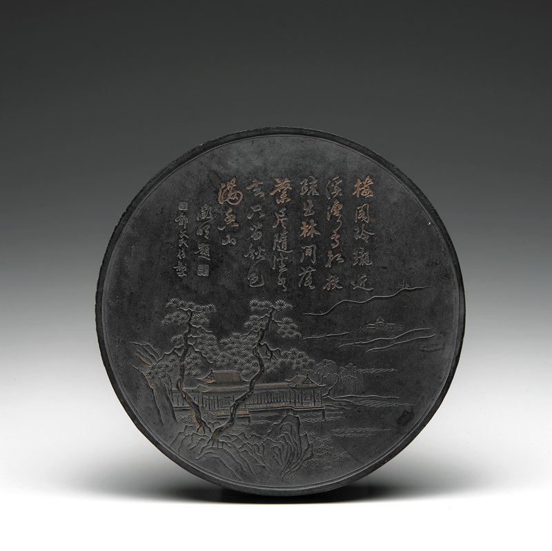 circular black ink cake with gilt highlights; landscape with trees, building and water on front, with inscription at top; inscription on back surrounded by dragons in swirling clouds