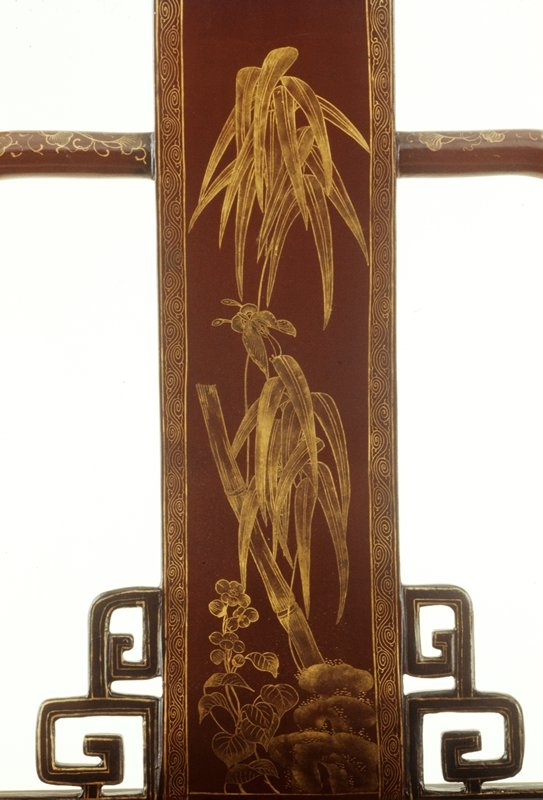 brown lacquer with a high scrolling central splat decorated with gold lacquer