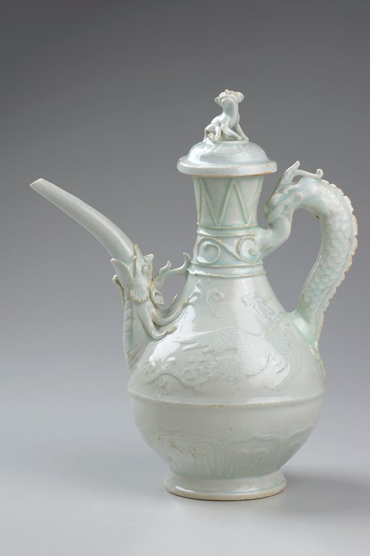 bulbous body with long, thin neck; spout carved with dragon's head; handle carved with dragon's head and neck; seated dog on top of cover; large bird carved on each side of body; light blue glaze