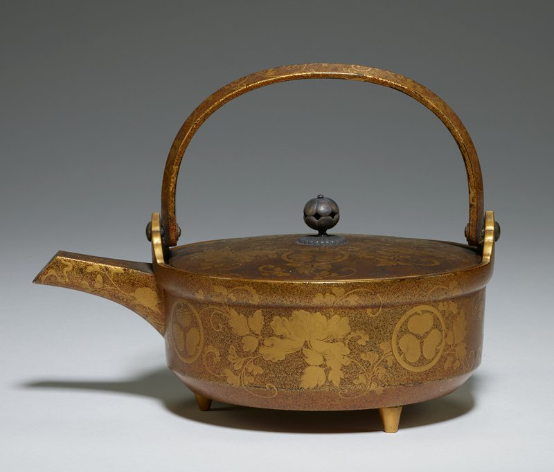 Sake pot, gold lacquer, with hinged semi-circular handle, and three short circular, tapering legs. Silver finial on cover. Decoration consists of gold vines, peonies, and arms of Tokugawa family (three asarum leaves within a circle) on bronze ground. Silver lacquer inside.