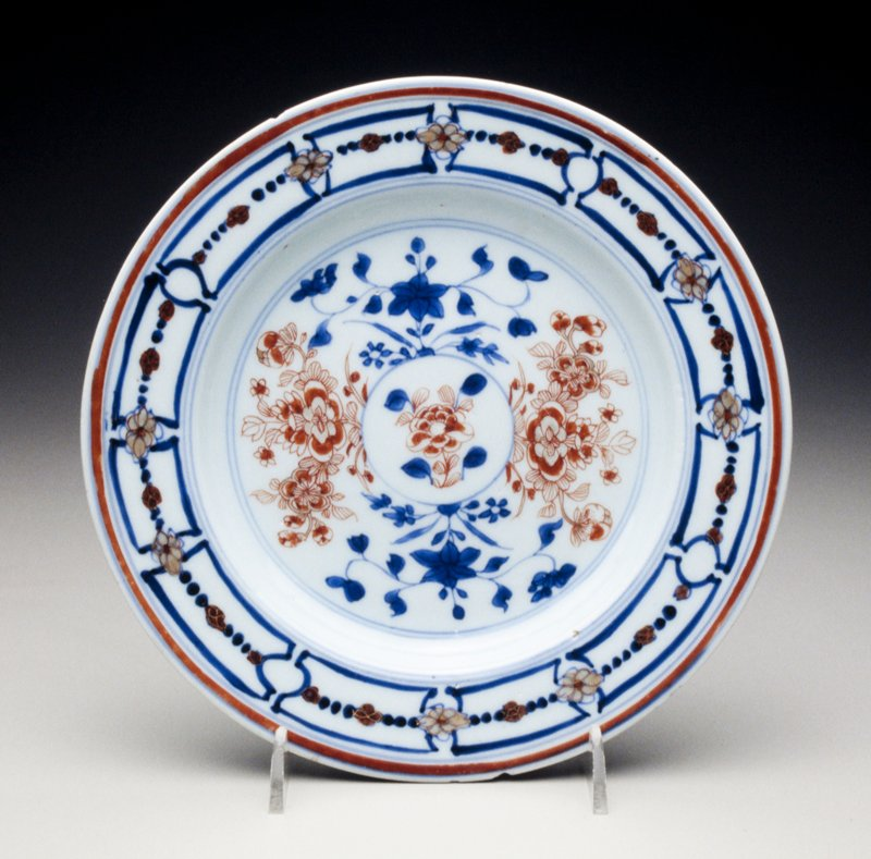 Imari plate with center gilt-heightened iron-red peony sprays, underglaze blue rim with panelled border, divided by gilt and iron-red blossoms and iron-red band