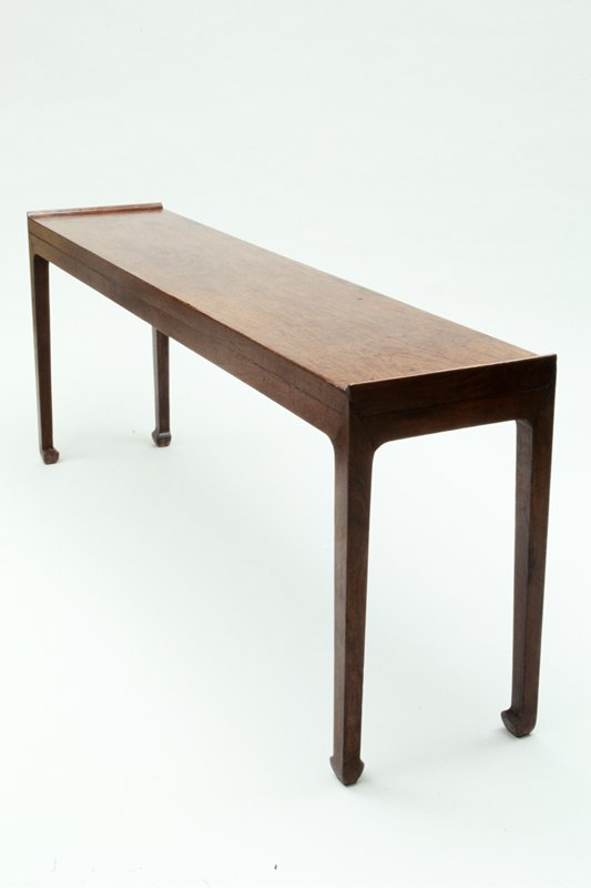 long narrow table unadorned; simple straight lines; wider feet; raised end pieces cover table top end grain and provide stops at each end