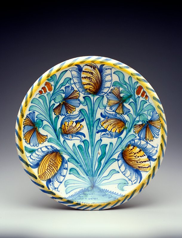 Title--tulip charger? Blue, yellow, green and brown floral design in basin with yellow and blue striping around rim; unadorned sides