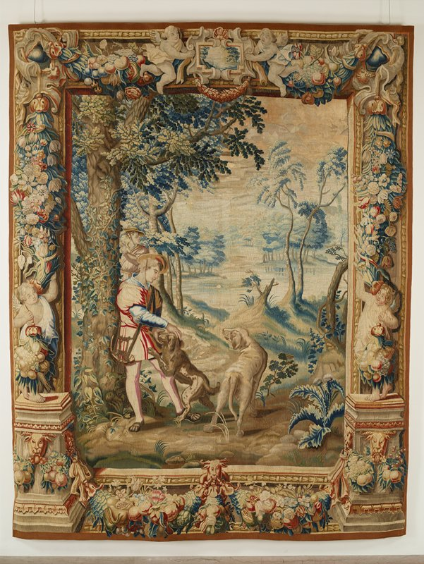 Set of four tapestries, with landscape scenes and figures inspired from the Hunts of Maximilian, now in the Louvre and woven after the cartoons of Bernard Van Orley, also preserved in the Louvre. Woven at sides with bases sustaining figures of putti and decorated with ram's heads. Embellishment of festoons, pendant bunches of fruits and flowers. Top border with scrolled, oblong cartouche in center, which contains a miniature landscape scene, supported by winged cherubs. Similar cartouche, with swags of fruit and flowers in bottom border. .1 Awaiting the Chase In the immediate foreground trwo huntsmen, one of whom reclines against a tree and caresses a hound. The hunters wear short doublets and broadrimmed hats. Hunters' horns are slung over their shoulders.; warp undyed wool, 7-8 ends per cm., weft dyed wool and silk, 24-40 ends per cm.