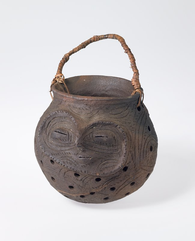 spherical vessel with outward flaring lip; holes punctured throughout; 2 heart-shaped faces with pursed lips carved into opposite sides