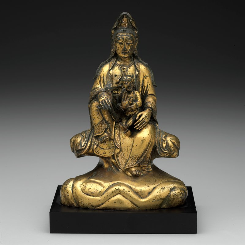 gilt bronze female figure seated on cushion holding small male figure in lap; mounted on black stand
