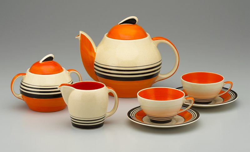 nearly spherical body with wide foot; wedge-shaped finial on domed cover; handpainted; orange at handles, on cover and stripe at bottom; black on finial and 4 black stripes of various widths on body; cream ground