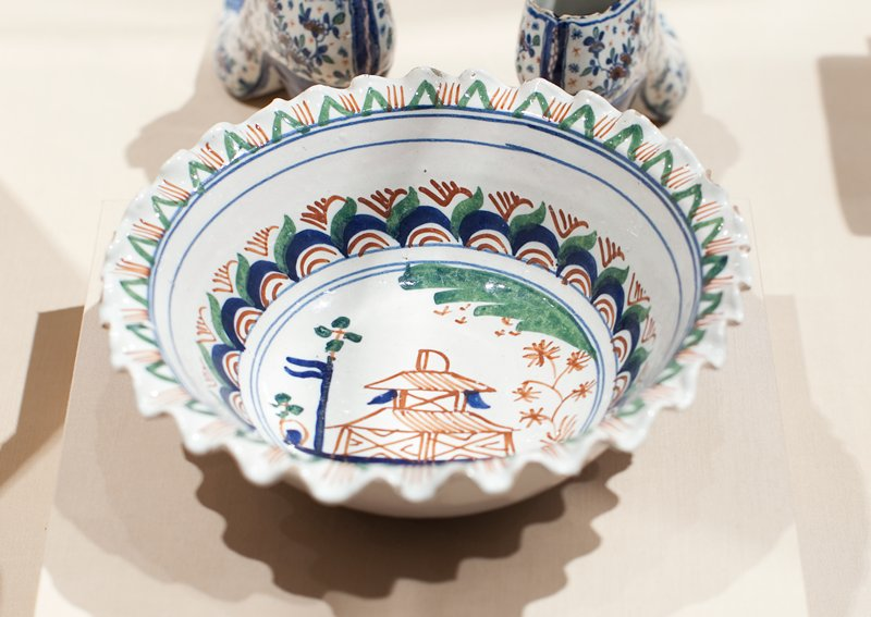 ceramic bowl with pinched rim; central design of a Chinese house bordered by a blue and red half circle design