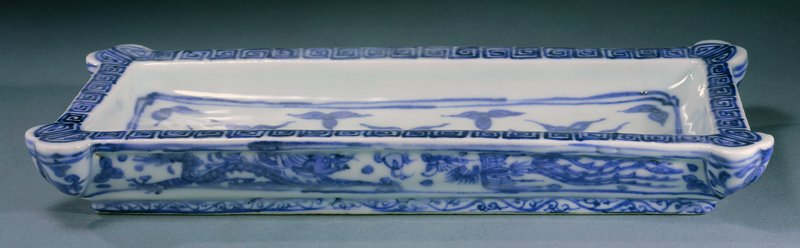 blue and white; flat rim with rounded corners and meander design; organic design inside center framed by two lines, dragons on sides; has its own box