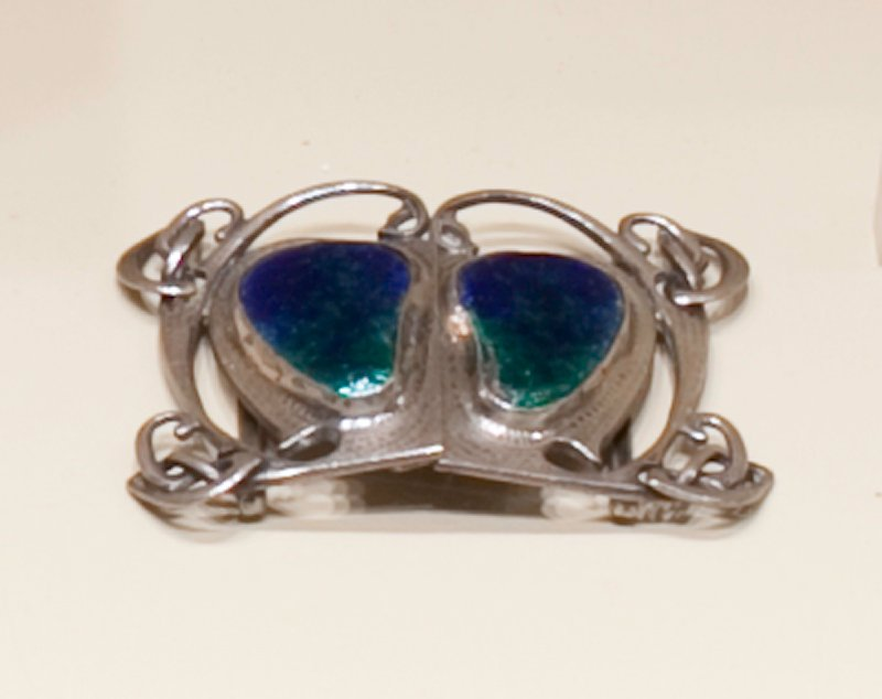 silver belt buckle; organic motif; two kidney bean shaped enamel inserts at center with blue merging into green enamel