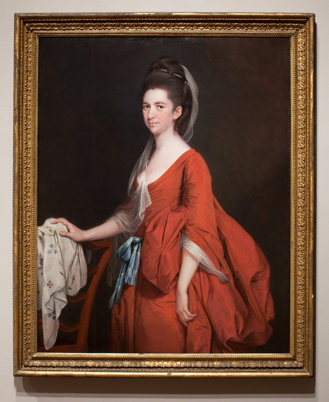 Portrait of a woman in red dress, cut low at the neck, with blue sash; white muslin veil falling from her hair; resting her right hand upon the back of a chair.