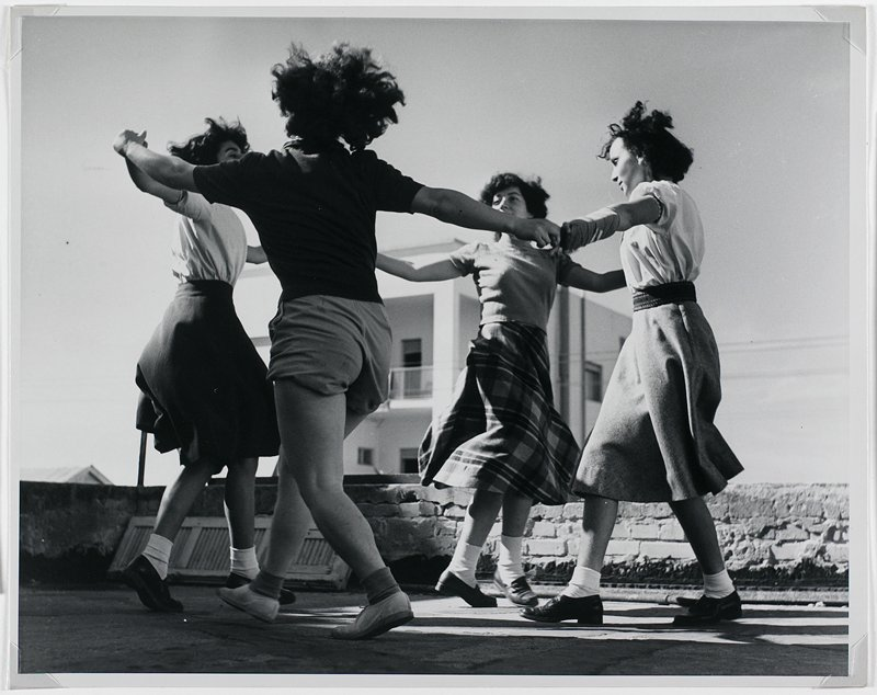 black and white photograph of girls dancing in a circle in front of brick wall