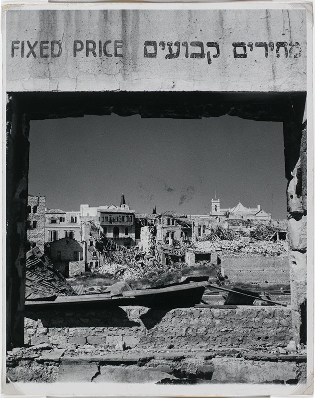 "bombed buildings and rubble seen through an opening with a sign ""Fixed Price"" above"