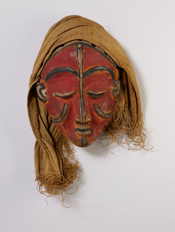 female face with closed eyes, long nose and small ears; red with black details; cloth over head