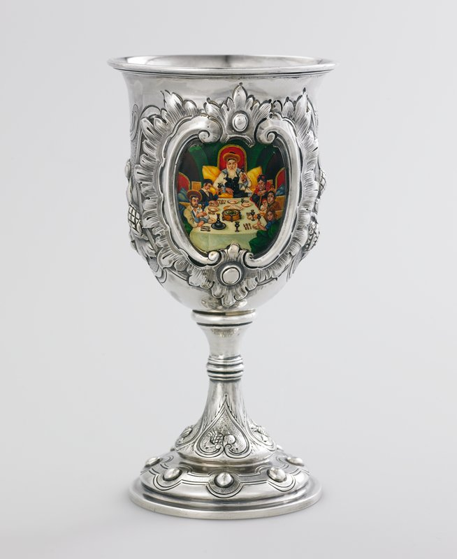 silver cup on pedestal foot with repousse and enamel decoration; design of fruits with painted scene in cartouche of seder
