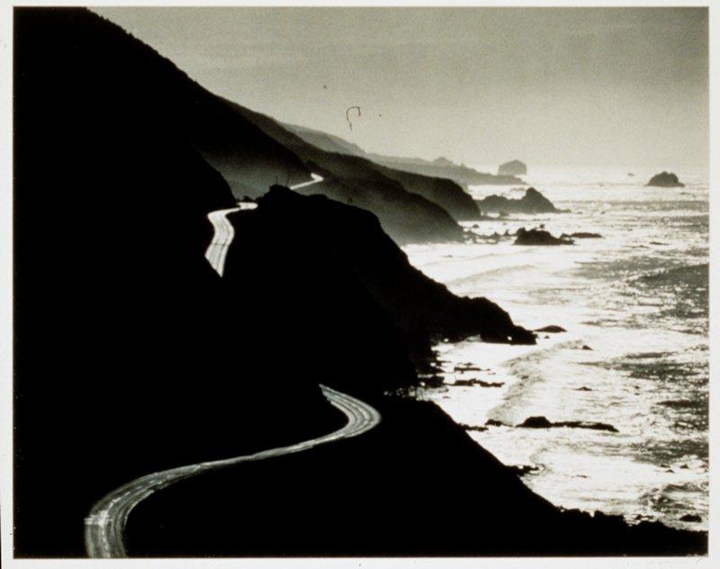 winding road on hillside by ocean
