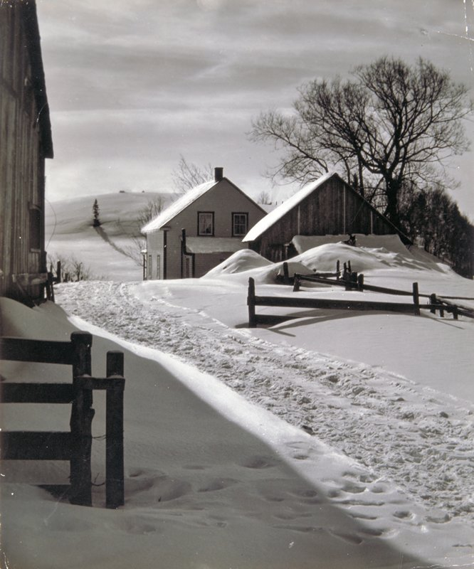 farm house with building in front and another building at left; fences and tracks in snow; bare trees at left