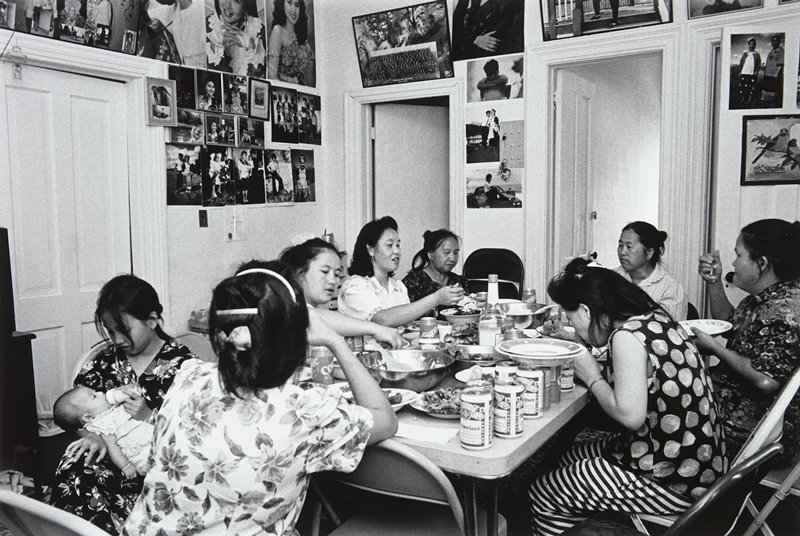 black and white photo of eight women eating seated around table