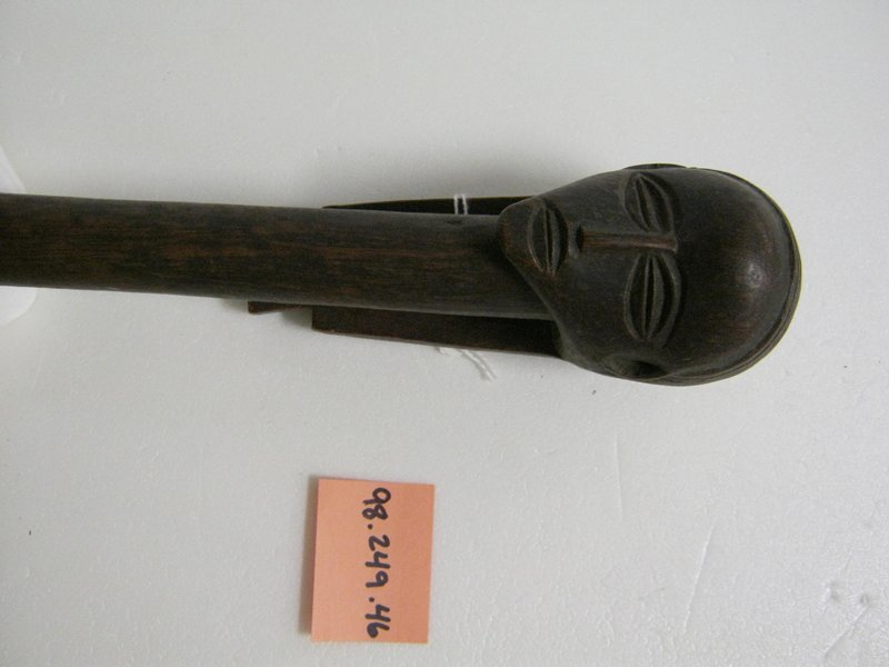 Straight, undecorated staff with head at top wearing a hairstyle with two long tails attached together at the bottom