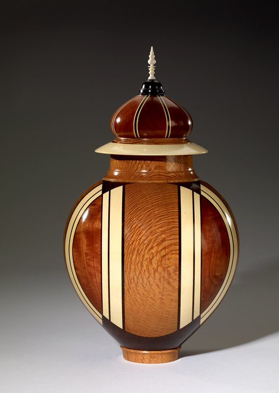 urn with lid; brown, black, and white; urn has four pairs of vertical white stripes curved together at top and bottom; lid has eight black and white stripes, a thin pointed white finial, and a wide white band at the bottom