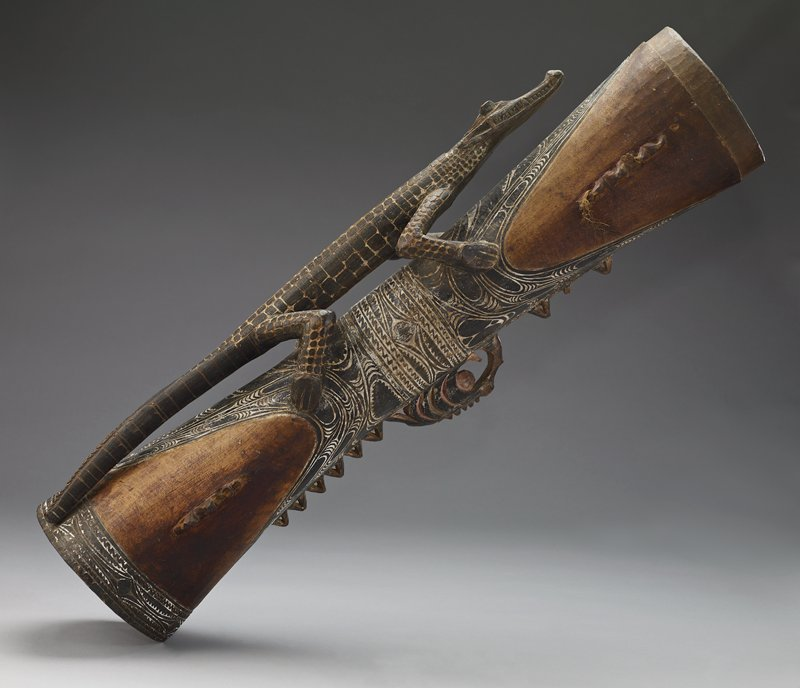 long cylinder, ends conical shaped; alligator stands along top facing drum surface; sets of triangular shapes adorn sides and bottom, used to support drum when rope is strung through; low relief carving over body and alligator painted with black field and white recesses