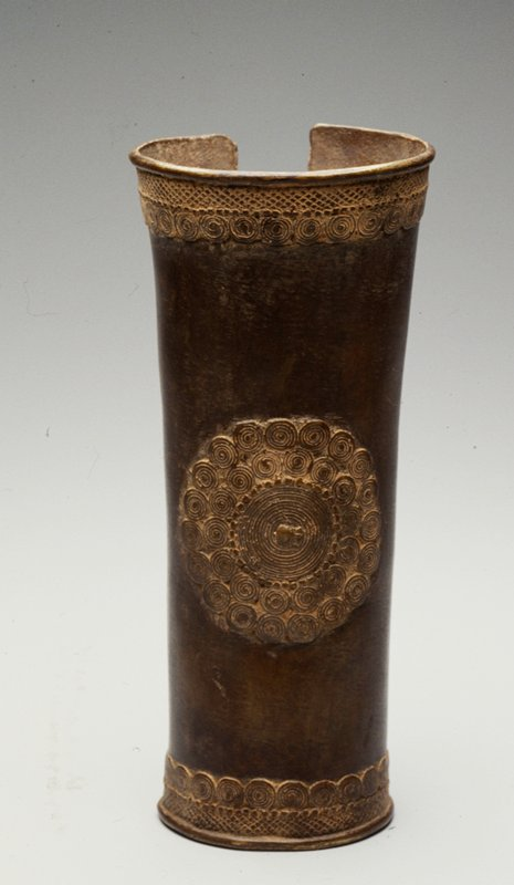 long bronze cuff with coiled circle designs around top and bottom edges; circular pattern in center