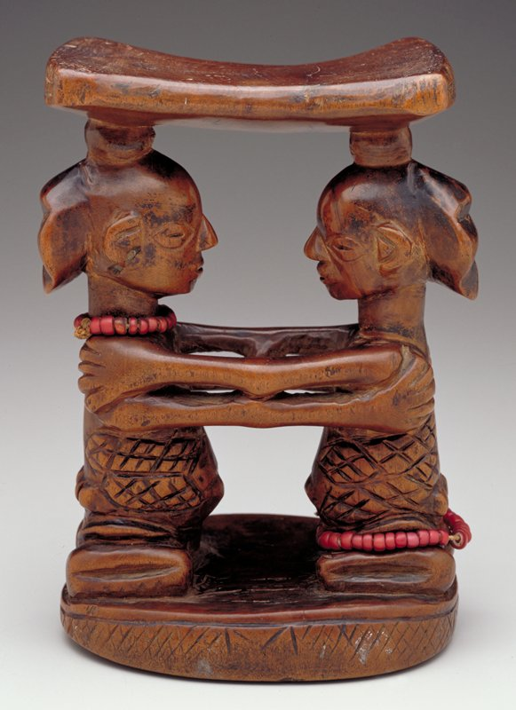 two female figures facing each other and embracing; string of red beads around feet of one figure and around neck of the other