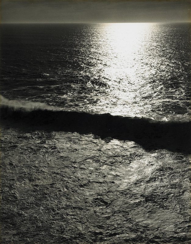 breaking wave with dark shadow; sun reflecting on water