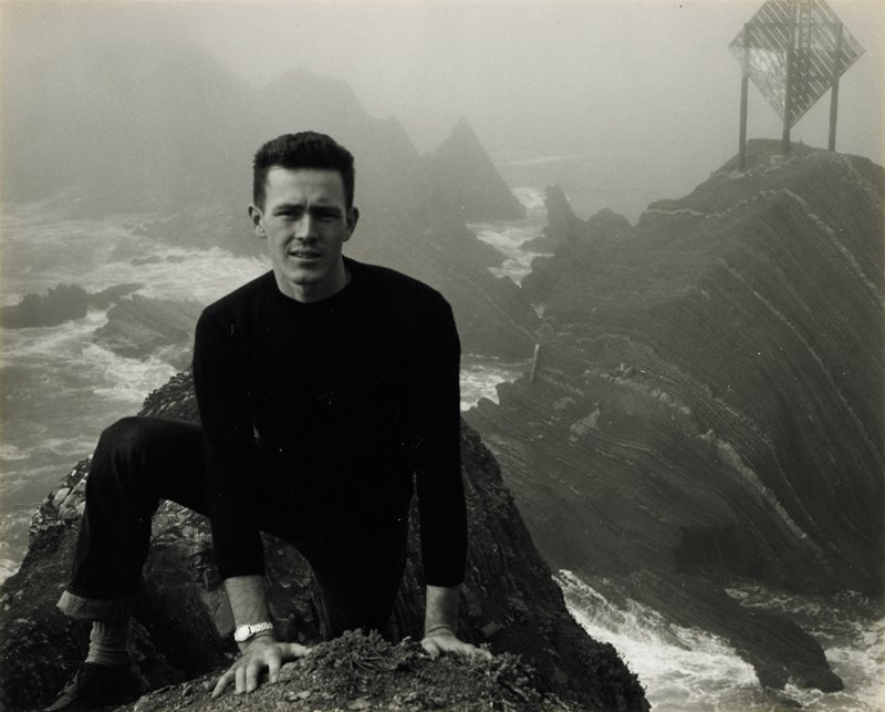 man in foreground wearing dark pants and a dark shirt, climbing on jagged rocks in water